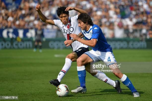 Sandro Tonali of Brescia Calcio competes with Takehiro Tomiyasu of Bologna FC during the Serie A match between Brescia Calcio and Bologna FC at...