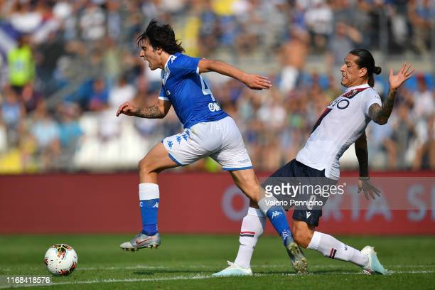 Sandro Tonali of Brescia Calcio is tackled by Federico Santander of Bologna FC during the Serie A match between Brescia Calcio and Bologna FC at...