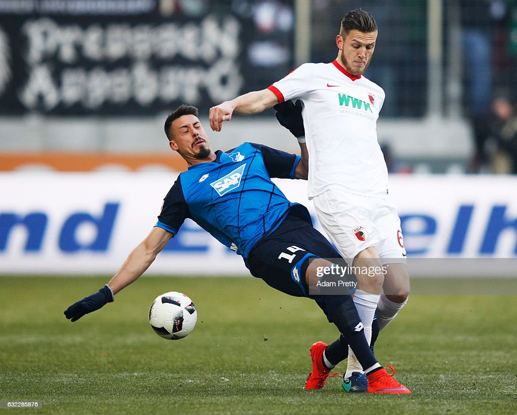Sandro Wagner of 1899 Hoffenheim tackles Jeffrey Gouweleeuw of Augsburg during the Bundesliga match between FC Augsburg and TSG 1899 Hoffenheim at WWK Arena on January 21, 2017 in Augsburg, Germany.