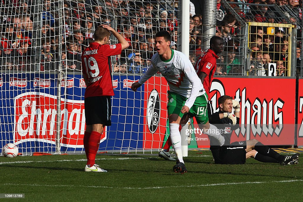 Sandro Wagner of Bremen celebrates his team's first goal as Papiss Demba Cisse, goalkeeper Oliver Baumann and Maximilian Nicu of Freiburg react during the Bundesliga match between SC Freiburg and SV Werder Bremen at Badenova Stadium on March 6, 2011 in Freiburg im Breisgau, Germany.