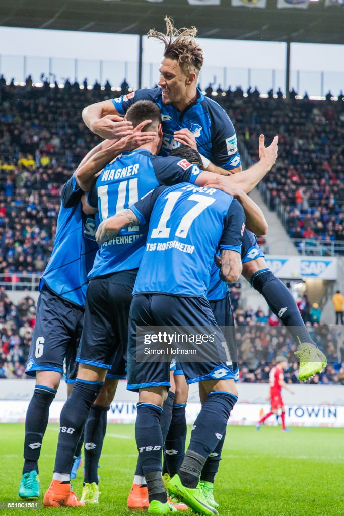 Sandro Wagner of Hoffenheim (L) celebrates his team's first goal with his team mates and Ermin Bicakcic (on top) during the Bundesliga match between TSG 1899 Hoffenheim and Bayer 04 Leverkusen at Wirsol Rhein-Neckar-Arena on March 18, 2017 in Sinsheim, Germany.