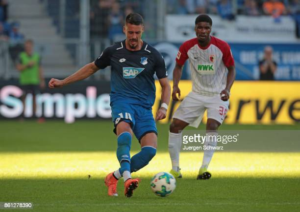Sandro Wagner of Hoffenheim passes the ball near Kevin Danso of Augsburg during the Bundesliga match between TSG 1899 Hoffenheim and FC Augsburg at...