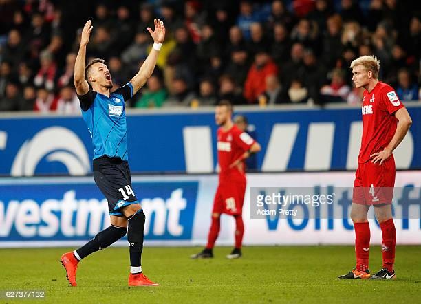 Sandro Wagner of TSG 1899 Hoffenheim celebrates scoring his second goal while Frederik Soerensen of FC Koeln is dejected during the Bundesliga match...