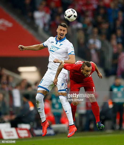 Sandro Wagner of TSG Hoffenheim jumps for a header with Rafinha of FC Bayern Muenchen during the Bundesliga match between Bayern Muenchen and TSG...