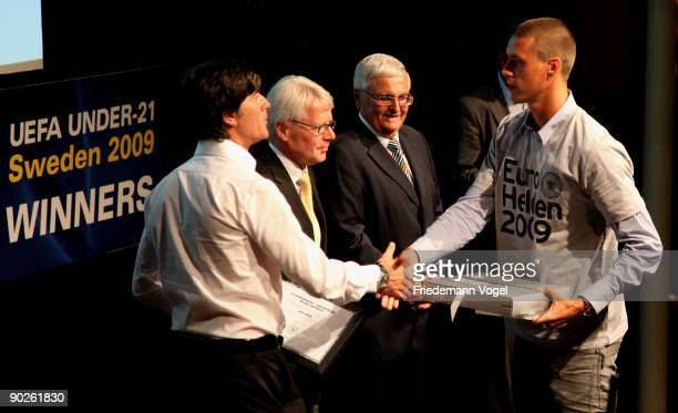 Sandro Wagner receives a trophy from Joachim Loew Reinhard Rauball and Theo Zwanziger during the distinction for the UEFA Under21 European Champion...