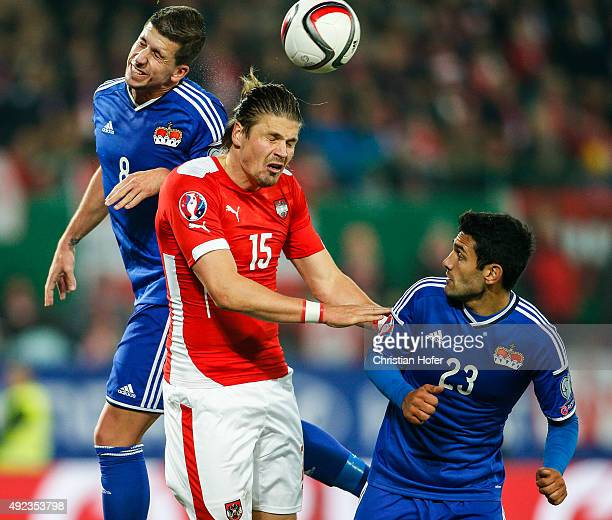 Sandro Wieser and Michele Polverino of Liechtenstein compete for the ball in the air with Sebastian Proedl of Austria during the UEFA EURO 2016...