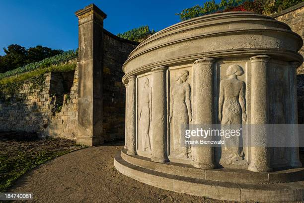 A sandstone artwork with different women sculptures is located at the base of a vineyard below the castle Lingnerschloss