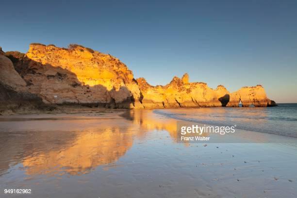 sandstone cliffs on the beach praia de tres irmaos at sunset, alvor, algarve, portugal - alvor stock pictures, royalty-free photos & images