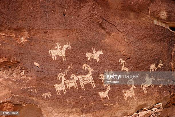 Sandstone Wall With Ancient Indian Writing Or Petroglyphs Showing Horses, Dogs, Ram And Hunting Scene. Southern Utah.