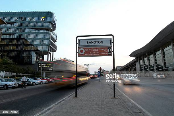 A Sandton sign stands on a central reservation between the offices of EY operated by Ernst Young Global Ltd left and the Gautrain station right in...