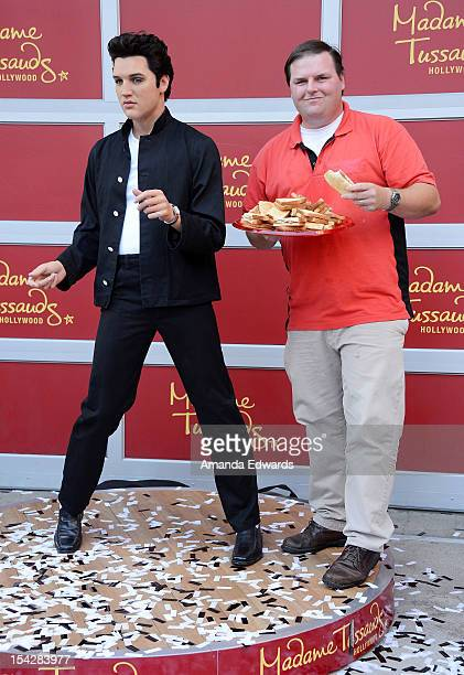 Sandwich eating contest winner James Donahue poses with a wax figure of Elvis Presley at the Madame Tussauds Hollywood unveils its firstever Elvis...