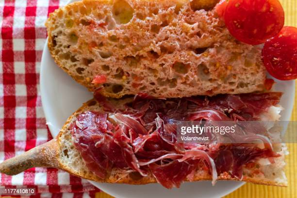 sandwich of bread with tomato, virgin olive oil and serrano ham breakfast - cultura mediterránea fotografías e imágenes de stock