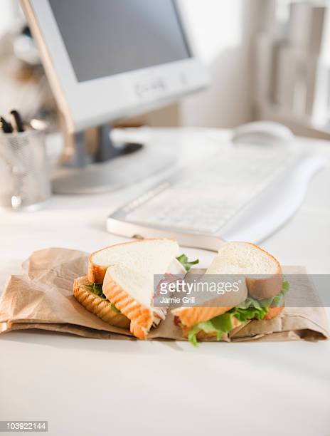 Sandwich on brown bag beside computer