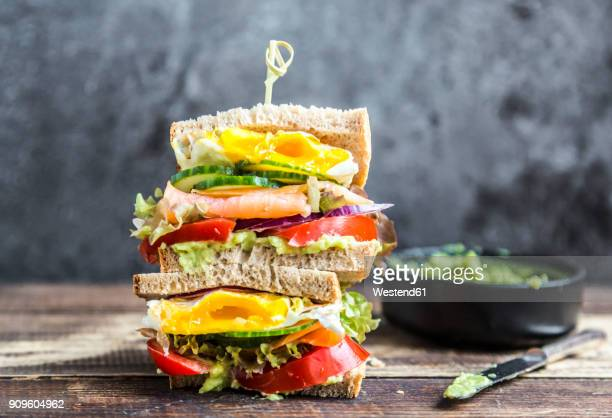 Sandwich with egg, salad, cucumber, tomate, salmon, avocado and onion