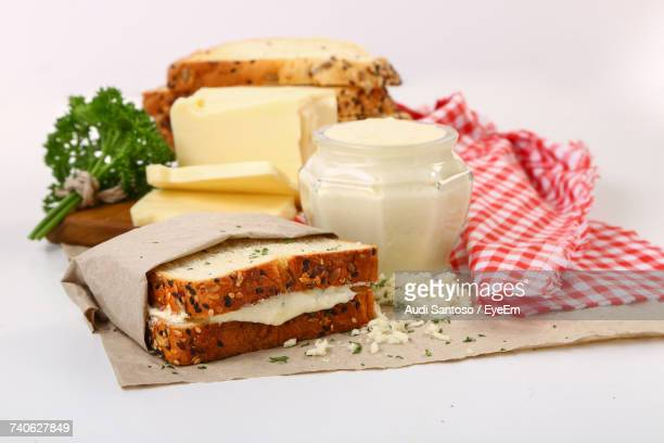 Sandwich With Ingredients On Wax Paper Over White Background