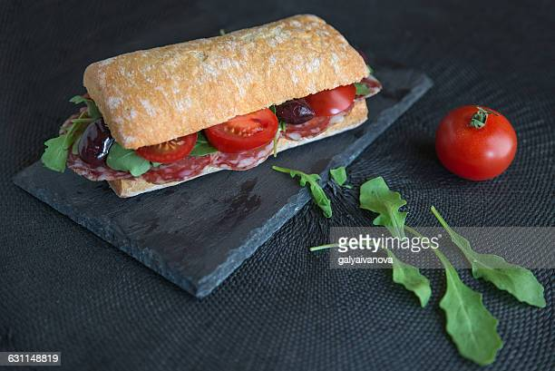 Sandwich with salami, tomatoes, olives and arugula