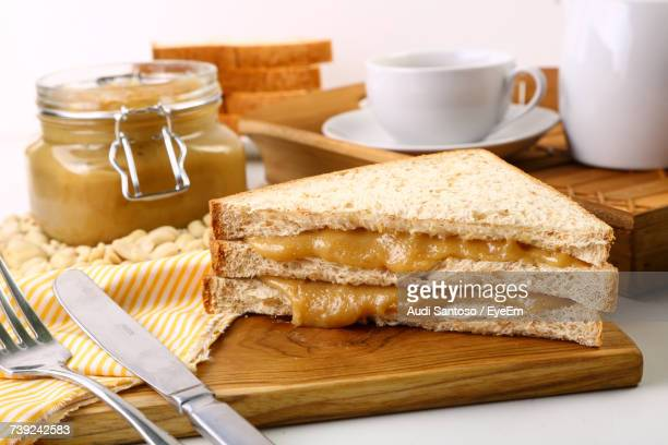 Sandwich With Tea Cup And Peanut Butter On Cutting Board Over White Background