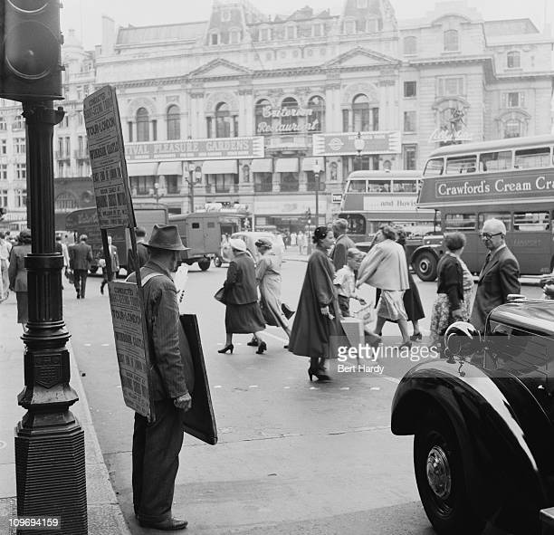 A sandwichboard man on Piccadilly Circus in London with the Criterion Restaurant in the background 1953 Original Publication Picture Post 6576 What...