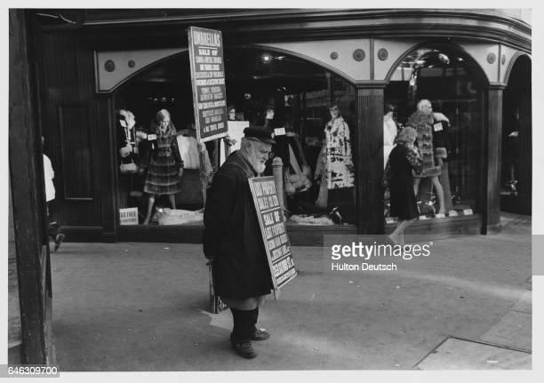 A sandwichboard man on the street