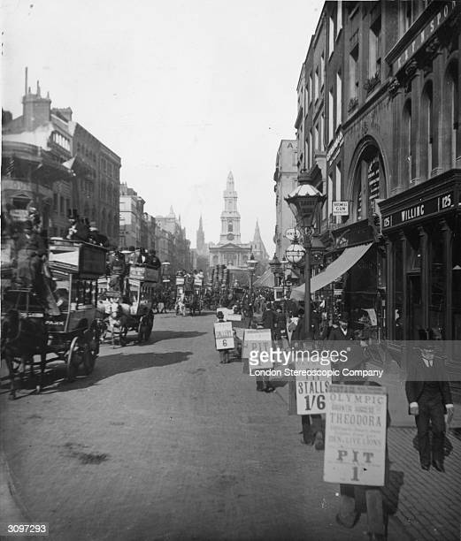 Sandwichboard men in the Strand advertise theatre seats Horse drawn buses fill the road and the church of St MaryleStrand is in the background