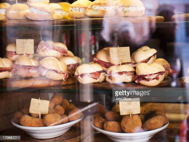 sandwiches and croquettes for sale in window - delicatessen stock photos and pictures