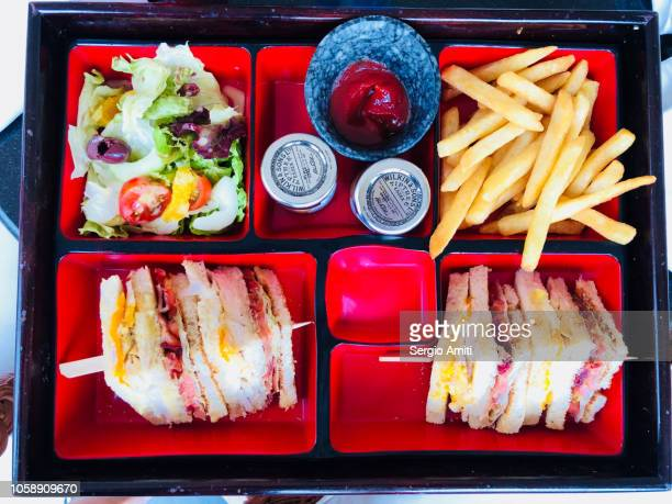 Sandwiches, fries and salad on red trays
