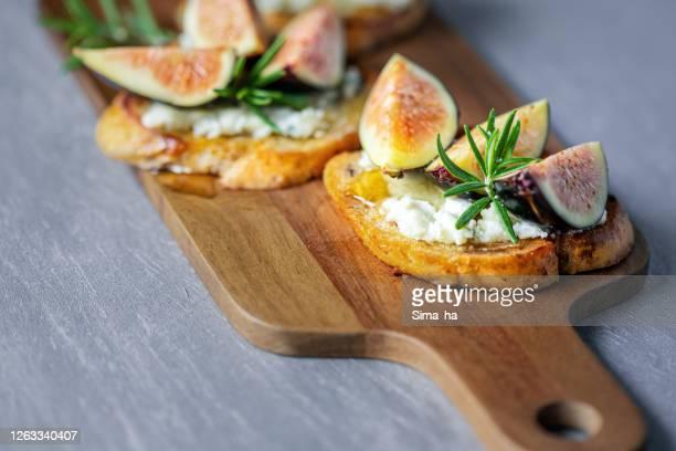 broodjes met verse vijgen, blauwe kaas, rozemarijn en honing op het snijden raad - blauwschimmelkaas stockfoto's en -beelden