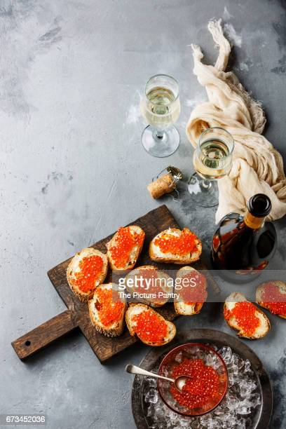 Sandwiches with salmon red caviar and champagne on concrete background copy space