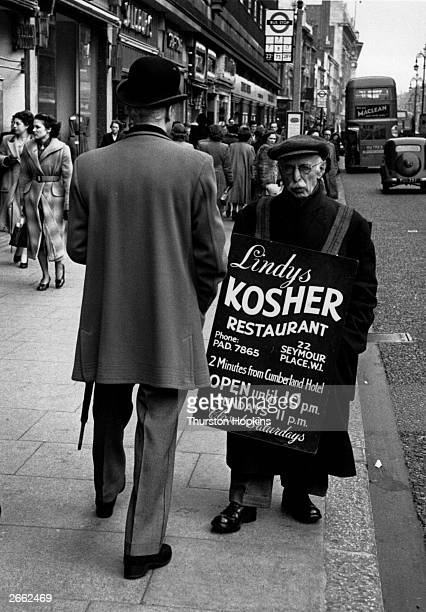 A sandwichman advertising a Kosher restaurant in London's Oxford Street Original Publication Picture Post 5884 The Dandy Comes Back To W1 pub 1952