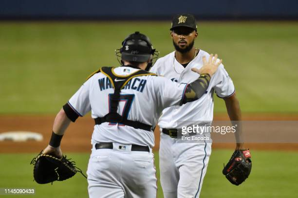 Sandy Alcantara of the Miami Marlins celebrates with catcher Chad Wallach after pitching a complete game against the New York Mets at Marlins Park on...