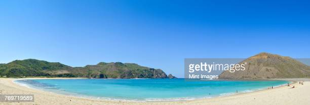 sandy beach and a view over the turquoise water in a protected bay and the headlands on the lombok coastline. - wide angle stock pictures, royalty-free photos & images