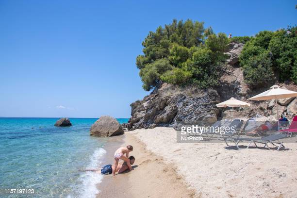 Sandy Beach and beach bar with sunbeds and umbrellas called Tortuga at Sithonia peninsula, Halkidiki, Greece on 17th July 2019. The beach with the...