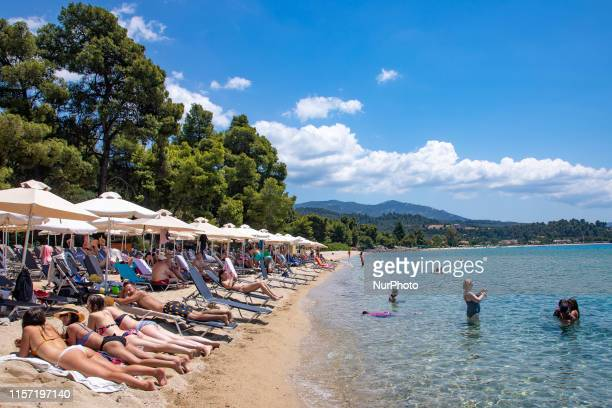 Sandy Beach and beach bar with sunbeds and umbrellas called Tortuga at Sithonia peninsula Halkidiki Greece on 17th July 2019 The beach with the...