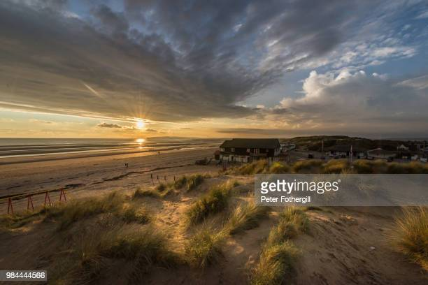 sandy beach during sunset in sussex, england. - camber sands stock photos and pictures