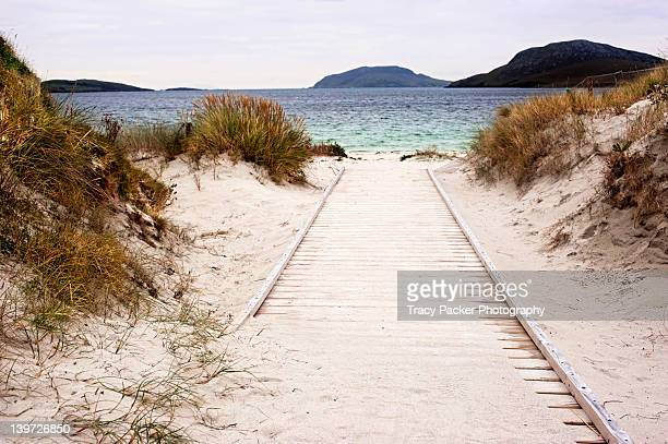 sandy boardwalk leading to sea - barra scotland stock pictures, royalty-free photos & images
