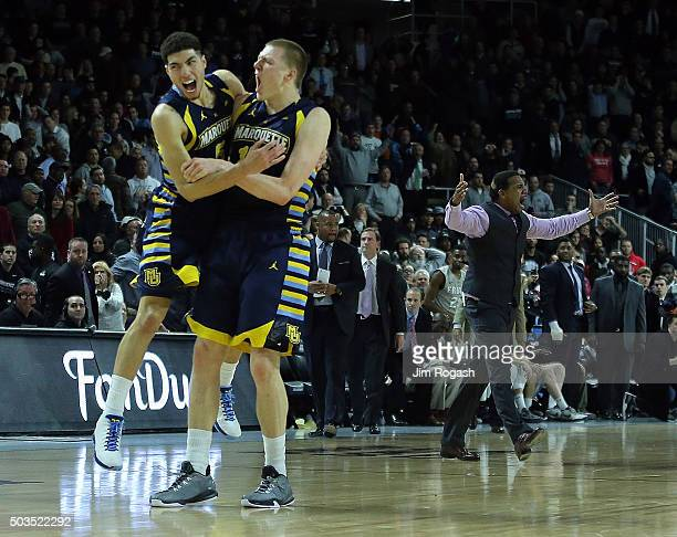 Sandy Cohen III of the Marquette Golden Eagles and Henry Ellenson celebrate after defeating Providence Friars 6564 as Ed Cooley of the Providence...