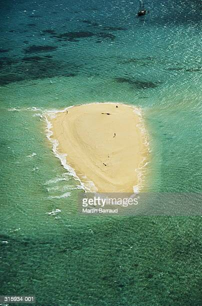 Sandy coral island (cay) in turquoise ocean, aerial view