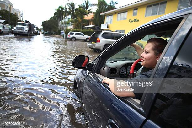 Sandy Garcia sits in her vehicle that was stuck in a flooded street caused by the combination of the lunar orbit which caused seasonal high tides and...