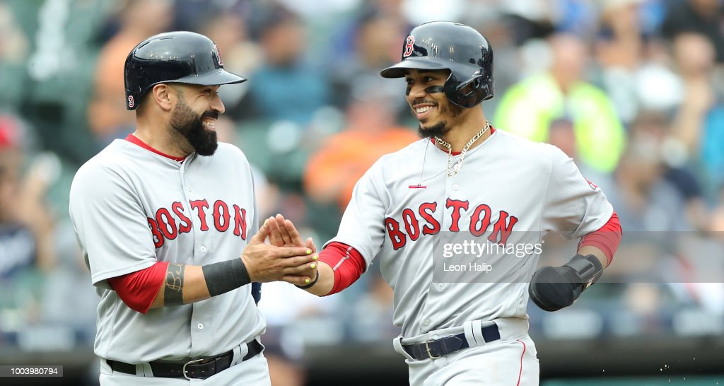 Sandy Leon #3 and Mookie Betts #50 of the Boston Red Sox celebrate after scoring on the triple by Andrew Benintendi (not in photo) in the seventh inning of the game against the Detroit Tigers at Comerica Park on July 22, 2018 in Detroit, Michigan.