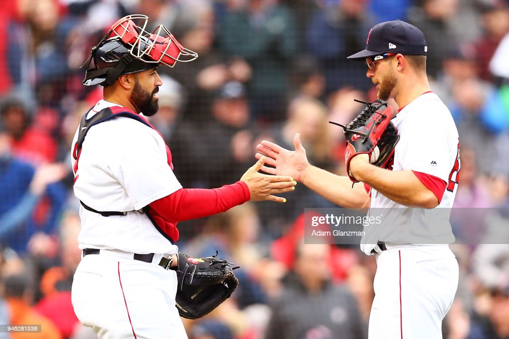 Sandy Leon #3 high fives Marcus Walden #64 of the Boston Red Sox after a victory over the Baltimore Orioles at Fenway Park on April 14, 2018 in Boston, Massachusetts.