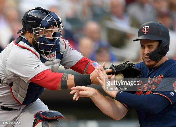 Sandy Leon of the Boston Red Sox defends home plate against CJ Cron of the Minnesota Twins during the first inning of the game on June 19 2019 at...