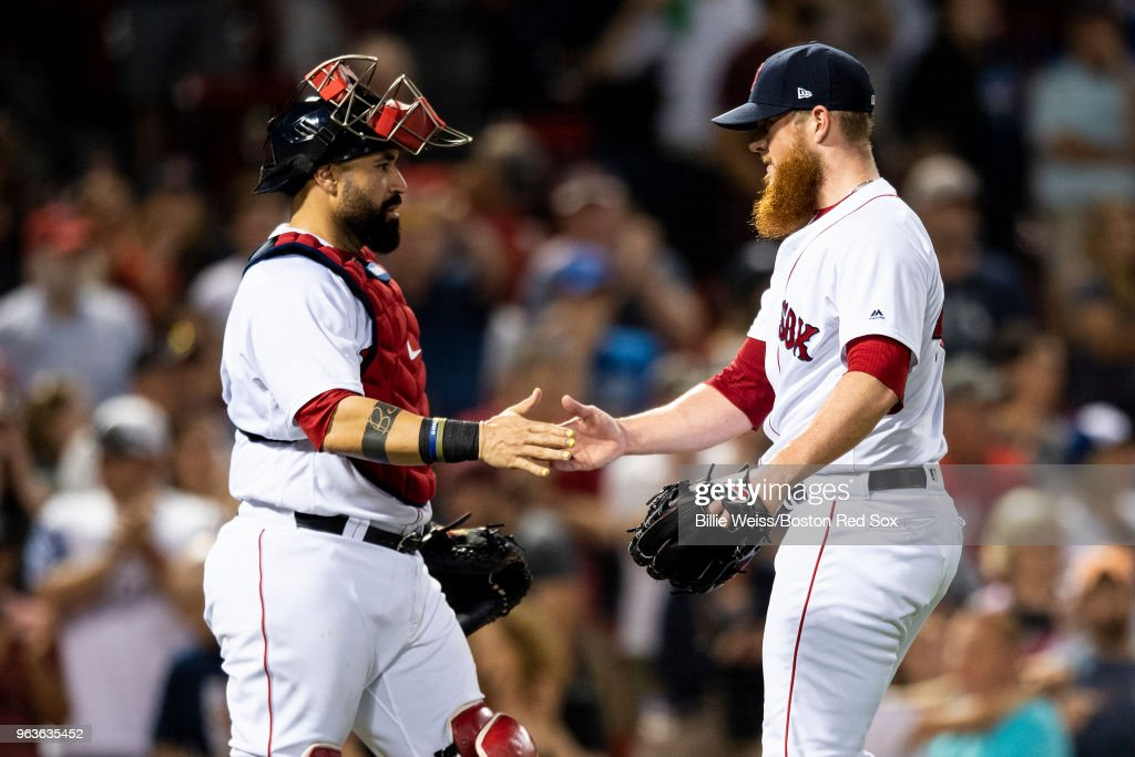 Sandy Leon #3 of the Boston Red Sox high fives Craig Kimbrel #46 after recording the final out of a game against the Toronto Blue Jays on May 29, 2018 at Fenway Park in Boston, Massachusetts.