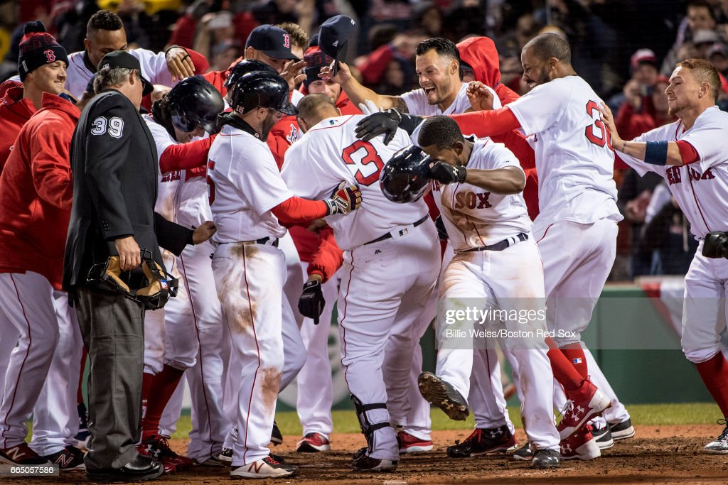 Sandy Leon #3 of the Boston Red Sox is mobbed by teammates after hitting a walk off three run home run during the twelfth inning of a game against the Pittsburgh Pirates on April 5, 2017 at Fenway Park in Boston, Massachusetts.