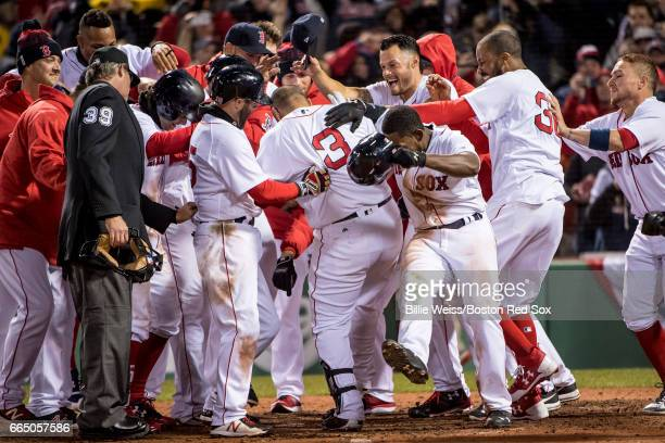 Sandy Leon of the Boston Red Sox is mobbed by teammates after hitting a walk off three run home run during the twelfth inning of a game against the...