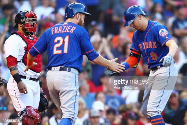 Sandy Leon of the Boston Red Sox looks on as Brandon Nimmo high fives Todd Frazier of the New York Mets after hitting a threerun home run in the...