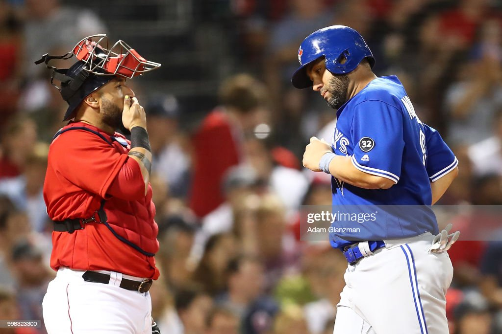 Sandy Leon #3 of the Boston Red Sox looks on as Kendrys Morales #8 of the Toronto Blue Jays crosses home plate after scoring in the eighth inning of a game at Fenway Park on July 13, 2018 in Boston, Massachusetts.