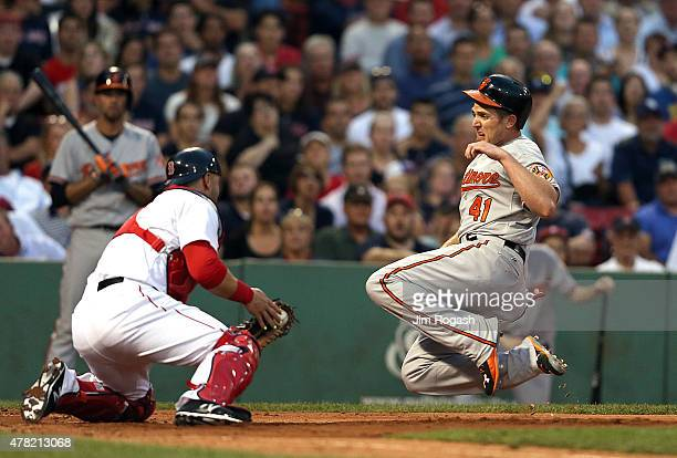 Sandy Leon of the Boston Red Sox prepares to tag out Chris Parmelee of the Baltimore Orioles trying top steal home in the third inning at Fenway Park...