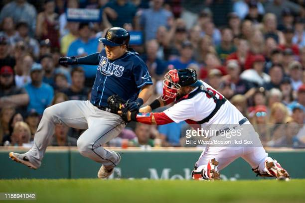 Sandy Leon of the Boston Red Sox tags out Ji-Man Choi of the Tampa Bay Rays during the second inning of a game on August 1, 2019 at Fenway Park in...