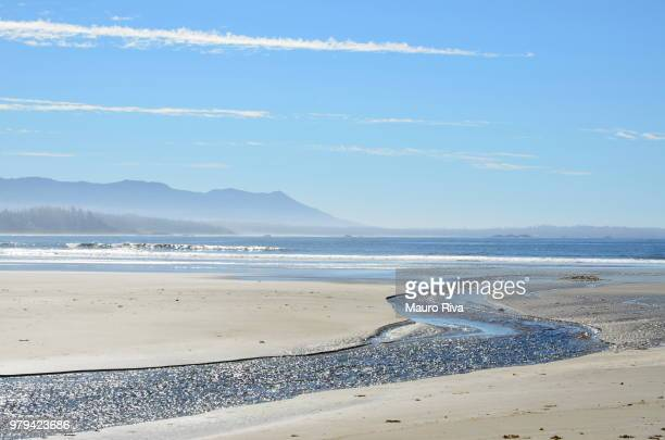 sandy long beach under partially clear sky, vancouver island, british columbia, canada - vancouver island stock pictures, royalty-free photos & images