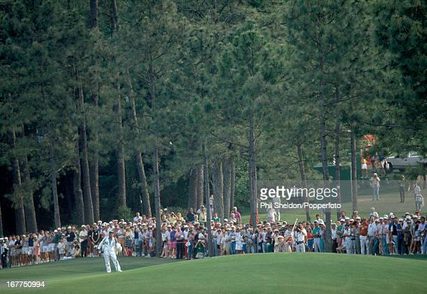 Sandy Lyle of Great Britain watched by his caddie Dave Musgrove shoots out of a bunker on the 72nd hole during the US Masters Golf Tournament held at...